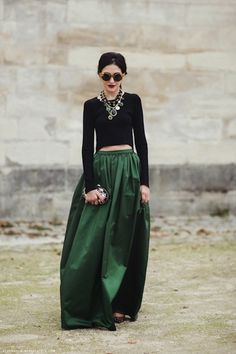 Cold weather cocktail attire. Full long skirt, cropped black sweater + piled on statement jewelry