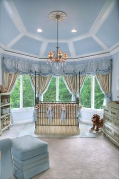 This royal prince nursery, designed by celebrity nursery designer Sherri Blum, features baby blue, creamy white and silver to give it an ethereal appeal. The high, angled ceiling called for custom crown molding, and a painted blue pennant was the perfect finishing touch to accentuate the room and provide a canopy over the space.
