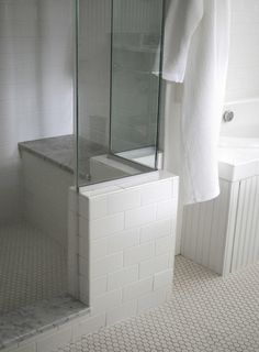 Master shower. LIke the gray top on bench and step. Also like the tile on the outside of the half wall.