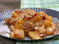 Low Fat Peach crumble  8 ripe peaches, peeled, pitted and sliced  Juice from 1 lemon  1/3 teaspoon ground cinnamon  1/4 teaspoon ground nutmeg  1/2 cup whole-wheat (whole-meal) flour  1/4 cup packed dark brown sugar  2 tablespoons trans-free margarine, cut into thin slices  1/4 cup quick cooking oats