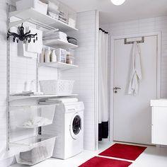 IKEA inspiration. Tvättstuga med vita vägghyllor, lådor i olika storlekar, stålskåp och en torkställning