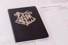 Give your favorite Harry Potter fan a journal with the Hogwarts crest front and center. Illustration is laser etched onto the cover of a Moleskine paper cahier notebook.  Dimensions: 3.5 x 5.5 Blank pages