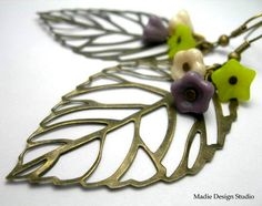 Large silhouette leaf in antique bronze with ivory green and   lavendar glass flower beads. Earwires are in antique bronze. MEMBER - madiedesignstudio