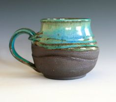 I like the different colors of the mug and how the color suddenly changes from a blue-ish green to brown. I also like the texture of the mug and how it's smooth at the top but rough at the bottom, giving the blue-ish green more of a shine. At the top of the mug, I really like how it  slightly curves in, giving it a neat look.