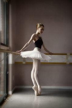 Portrait of a young ballerina en pointe illuminated by light streaming through a window model: Emily