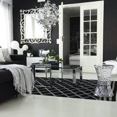 Kauniita yksityiskohtia ja ylellistä kiiltoa mustavalkoisen sisustuksen keskellä. Elegantti olohuone, josta löytyy paljon ihasteltavaa kuten mm. Kartell Stone jakkara ja Eero Aarnion Double Bubble valaisin.