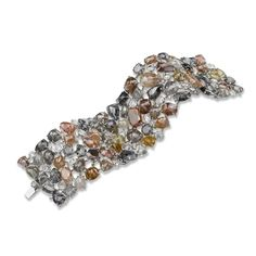 Crafted in 18k white gold is a Neda Behnam multi-cut rough diamond bracelet. Running through the whole bracelet is a variety of different shapes, sizes and colors of diamond. Elegant and stunning, this bracelet gives an air of supreme sophistication.