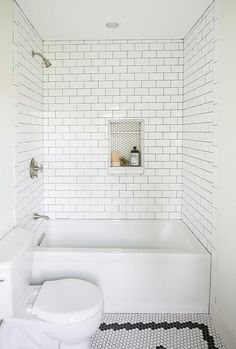 Black and white vintage hex floor tiles lead to a white drop-in bathtub fixed against white subway wall tiles fitted with a satin nickel shower kit and niche accented with white hex mini tiles. Tile Shower Niche, White Subway Tile Bathroom, Bathtub Shower Combo, Subway Tile Showers, Bathroom Tub Shower, White Bathrooms, Bathroom Black, Luxury Bathrooms, Master Bathrooms