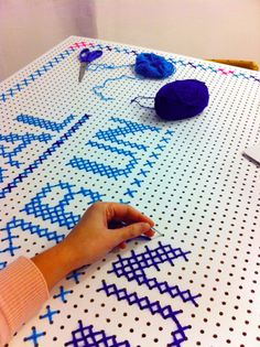 Cross stitch on painted peg board - this would be great to breathe life into a small side table