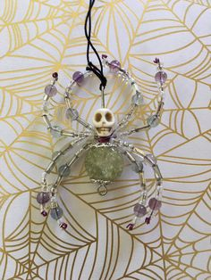 Beaded spider pendant with bendable legs and a bone skull head. Check out a…