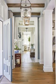 Our 2019 Idea House Is All About Neutral Paint Colors | When visitors open the front door and enter the house, they're greeted with an elegant, blue-and-white color palette, which echoes the paint colors used on the exterior. Neutral Sherwin-Williams shades lend the entry a sophisticated style. #decorideas #homedecor #southernliving