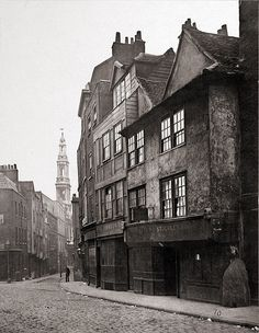 Old houses in Drury Lane, including the former 'Cock and Magpie' tavern (with sign). Photographed in 1876.