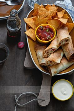 Chicken taquitos served tomato salsa, sour cream and tortilla crisps with a bottle of drink.