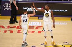 Stephen Curry of the Golden State Warriors and Kevin Durant of the Golden State Warriors high five on the court during the game against the Los...