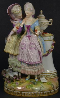 Antique Meissen German porcelain figure. Depicts two women in dresses standing near a column with urn and bows and arrows. Pigeons and flowers xan be seen at their feet. 19th century, 10 inches in height