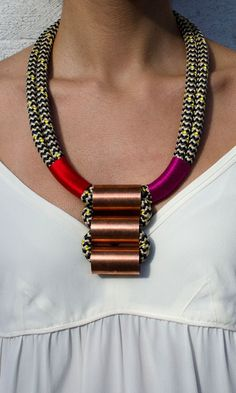 "Vibrant magenta and bright red thread are wrapped around this ladder necklace from Sepia Beauty, while thick climbing rope in black, yellow and tan is entwined with gilded copper tubes. An utterly unique statement piece that feels so-right-now.      -  12.5"" length"
