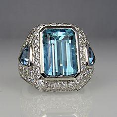 Emerald cut aquamarine centre stone and trilliant shaped   shoulder stones
