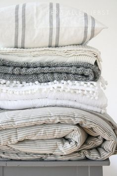 A Pile of white and grey squishy blankets, throws and pillow.