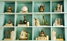 Robins Egg blue painted built ins.  Collection of antiques, brass, silver.