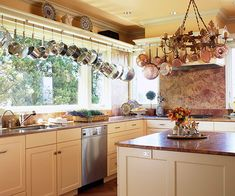 Pots and Pans Storage  Pots and pans are kitchen essentials, but their varying shapes make them difficult to store. Rather than filling kitchen cabinets with these cumbersome items, hang them close to the ceiling. Here, a ledge above the windows holds large platters while a bar with hooks holds hanging pots and pans.
