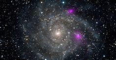 O observatório espacial de raios X NuSTAR detectou dois buracos negros (pontos roxos) na galáxia espiral IC 342, que fica na constelação da Girafa (Camelopardalis), a 7 milhões de anos-luz de distância da Terra. Os dois aparecem muito brilhante e mais claramente do que outros buracos negros de tamanhos similares, que pode ser o primeiro dos muitos mistérios que a equipe do NuSTAR espera resolver