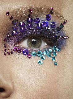 An array of amethyst, fuchsia and aqua jewels accent purple eye shadow.