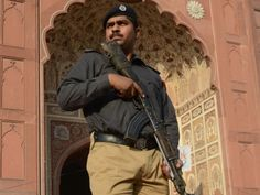 A policeman stands guard outside the Badshahi Mosque  during the Eid prayer in Lahore.