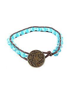 """<p>Brown cord bracelet from Disney's <i>Lilo & Stitch</i> with blue gem bead detailing and metal stitch face charm.</p>  <ul> <li>7"""" long</li> <li>Cord; plastic; alloy</li> <li>Imported</li> </ul>"""