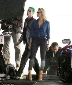 Bad style: Robbie wore tan boots, tight black jeans, a button down denim shirt and horn-rim glasses during the scene