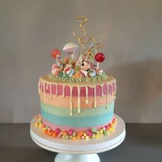 Pastel Rainbow Cake  Layers - alternate vanilla and chocolate Filling - white chocolate buttercream Frosting - almond buttercream Topping - white chocolate ganache, rainbow meringue kisses, lollipops, drumsticks, foam mushrooms, astrobelts and rainbow drops!