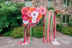 Take notes - this vibrant arbor (or chuppah) design with paper flowers, ribbon, and pinwheels is a super fun and creative way to add bright colors to a wedding ceremony! Check out the entire summer wedding at Willowdale Estate on our blog!