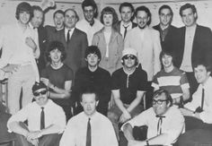 """The Beatles — and Neil Aspinall, at far right — sit with Lord Tim, KFWB, Los Angeles; Don Short, London Daily Mirror; Chris Hutchins, New Musical Express; Paul Drew, WQXI, Atlanta; Jerry G., WKYC, Cleveland; Marilyn Doerfler, Hearst; ""Reb"" Foster, KFWB; Ray Morgan, KGB, San Diego, Larry Kane, WFUN, Miami; and Jimm Stagg, WCFL, Chicago (back row) — and Alf Bicknell, publicity officer Tony Barrow, and road manager Mal Evans (front row)."""