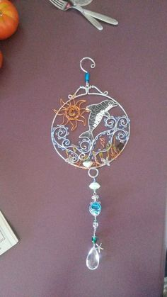 Wire wrapped beaded sun catcher with dolphin, seahorse starfish shells.