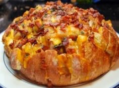 CHEESY BACON APPETIZER:   1 large unsliced round sourdough bread,  8 ozblock of cheddar cheese,  1/4 lb bacon,  1 stick butter,  1/4 tsp each dried chives, parsley, dill weed, & garlic powder,  1/8 tsp each onion powder, salt & pepper