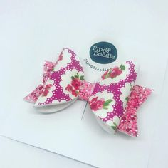 A beautiful hand crafted large sized bow made by Pip and Doodles fair hands in our Yorkshire HQ. Pink Floral Fabric with glitter back Hair Bow backed onto Clip Barrette. Pip and Doodles Bows measures approx 3 / 76mm Safety Notice Our lovely handmade products are intended to be