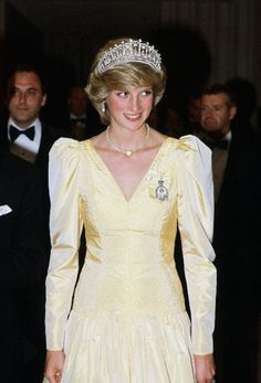 une 1983 In a yellow satin dress, pearl-and-diamond Cambridge Tiara, and heart-shaped necklace given to her by Prince Charles after the birth of their first son while attending a banquet in Canada. Yellow Satin Dress, Blue Sequin Dress, Red Polka Dot Dress, Metallic Dress, Satin Dresses, Princesa Diana, Royal Blue Skirts, Celebrities Who Died, Princess Diana Fashion