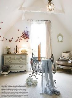 Baby nursery with butterflies on the wall and an iron bassinet.