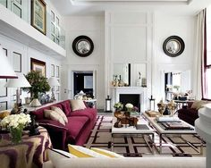 Pablo Paniagua living room--bold white and raspberry color palette, velvet sofa, skirted side table, double coffee tables, geometric rug