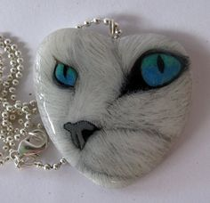 This is a cheeky, blue eyed cat painted on a heart shaped stone pendant. The heart shaped stones are from Italy. It is painted using high quality