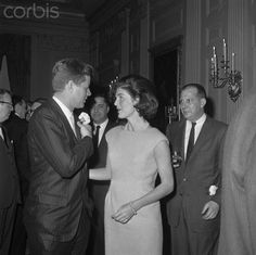 The position of First Lady, of being constantly in the public eye, is a demanding one. One of the prime functions of the President's wife is to serve as hostess at numerous dinners and other gatherings. Here, Mrs. Jacqueline Kennedy, a charming and gracious hostess, gets a kiss from her step-uncle, Wilmarth Lewis, of Farmington, Conn., as the latter arrives to attend a Congressional Coffee Hour at the White House. They are seen outside the state dining room. 06 May 1961