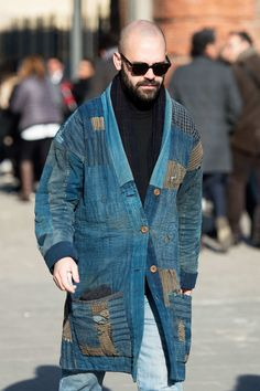 Wearing his grandmas hippie handmade 60s denim patchwork coat, this gentleman loves doilies too, at Pitti Uomo