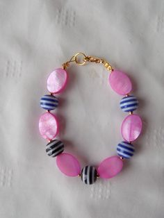 Bracelet enfant réalisé en perles : perles palets ovales rose nacré Perle spirale bleu/blanc et noir/blanc  Fermeture par mousqueton doré Monté sur fil câblé, très ré - 11757091