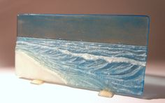 This glass panel illustrates the seaside using low relief and colours to accentuate the motion of the waves and create a dramatic effect. Some parts