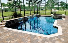 Geometric swimming pool with cascade waterfalls, elevated spa, and paverstone deck.