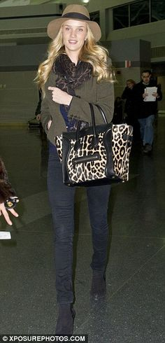 Rosie Huntington-Whiteley at JFK's airport terminal in black skinny jeans, an olive green coat, brown fedora, and black suede Chelsea boots.