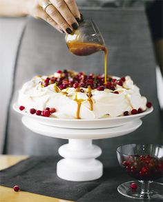 A dessert cake Pavlova, with hot caramel and frozen cranberries
