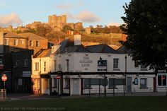 Autumn Sunset of Dover Castle from the Golden Lion, Kent, England, UK. Victorian Golden Lion public house at 11 Priory Street and Priory Place established pre-1846; in 1881 the pub opened at 5 am. To the right is Roy's Mens Hairdressers (Barbers). Skyline: Norman Keep, Inner Curtain Wall, and Western Outer Curtain Wall of Dover Castle (Peverell's Gate, Constable's Gateway, Colton Tower). A256/B2011 Folkestone Road roundabout. Urban Dover History photo. See…