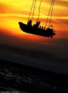 Daring procedure: Royal Marines attach their Rib boat to strops lowered from a helicopter before being lifted. Swing.