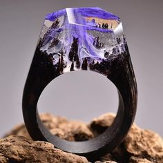 The jeweler Secret Wood (previously) has been producing even more miniature cities and landscapes, each ethereal universe living inside a resin geometric dome on top of their handmade wooden rings. In addition to buildings set against swirling skies, there are also works that contain tiny flowers, p