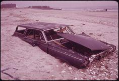 Sand covers an abandoned car on a Breezy Point beach.